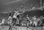 American professional basketball player Bill Russell of the Boston Celtics leaps leaps with arm outstretched to block a shot from an opponent during...