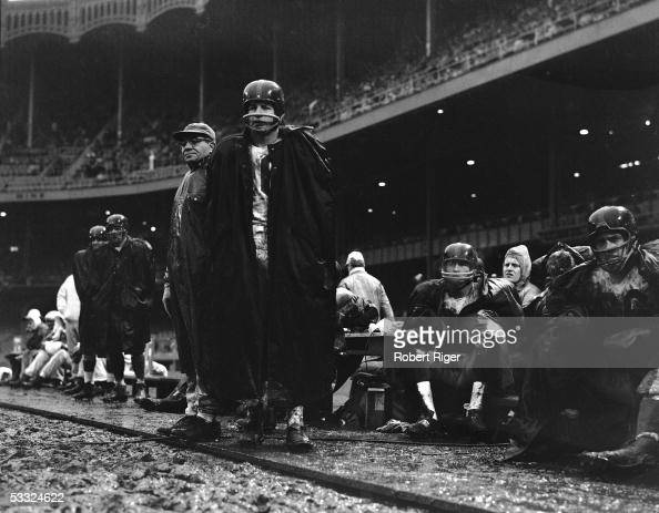 American professional football coach Vince Lombardi and player Frank Gifford of the New York Giants watch a game from the muddy sidelines Yankee...