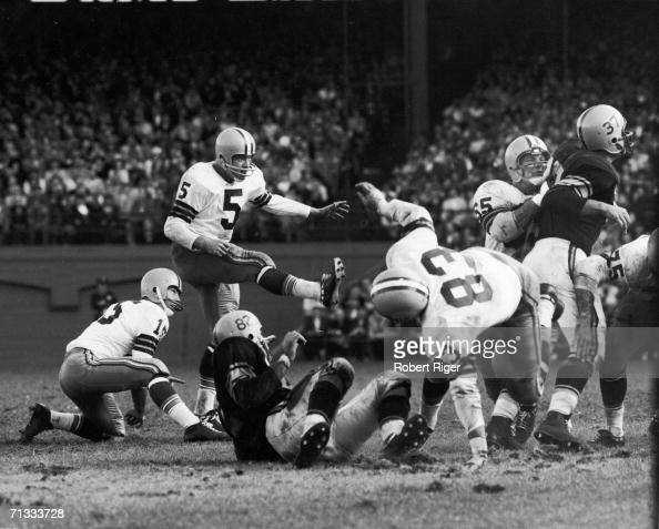 American professional football player Bart Starr quarterback for the Green Bay Packers kneels and watches as running back Paul Hornung attempts a...