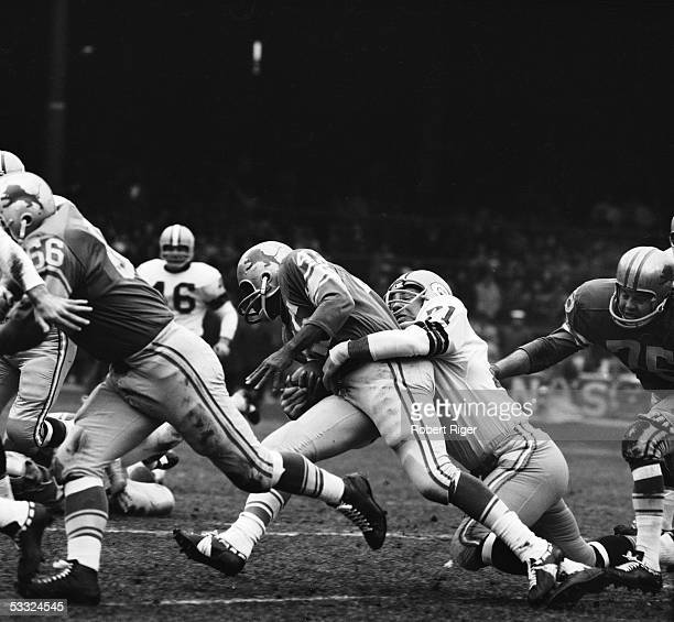 American professional football player Bill Forester of the Green Bay Packers throws himself desperately around the legs of the Detroit Lions ball...