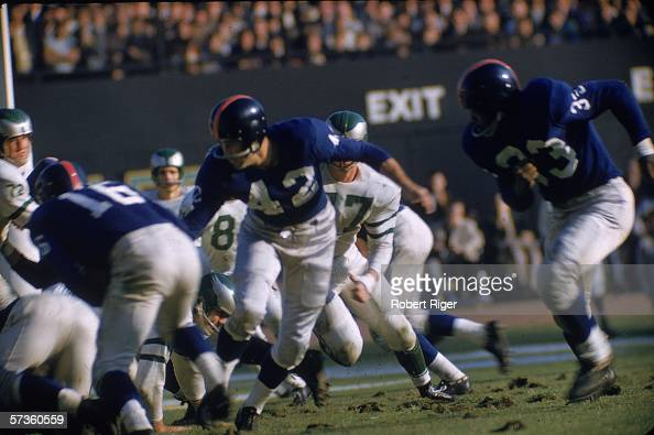 American professional football player Charlie Conerly quarterback of the New York Giants hands off to Frank Gifford as teammate Mel Triplett runs...
