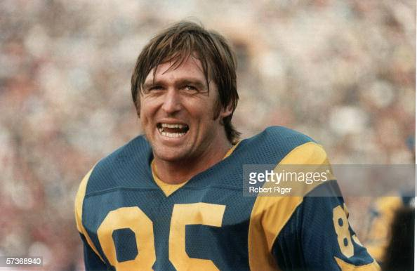 American professional football player Jack Youngblood chews gum and laughs on the sidelines during a game 1970s