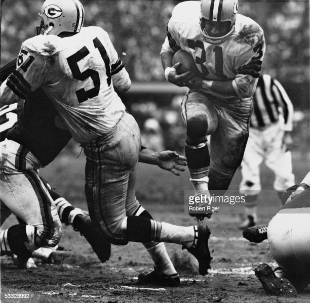 American professional football player Jim Taylor of the Green bay Packers runs with the ball through a gap in the defensive line of the Cleveland...