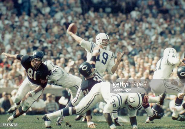American professional football player Johnny Unitas quarterback for the Baltimore Colts cocks his arm to throw the ball from the midst of a tangle of...