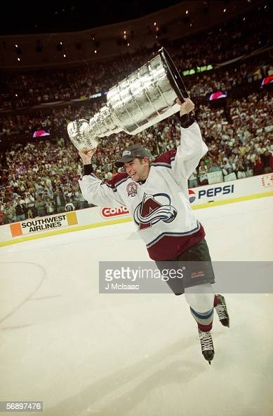 American professional hockey player Chris Drury of the Colorado Avalanche skates around the rink with the Stanley Cup over his head in celebration of...