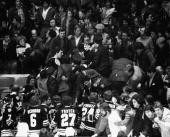 American professional ice hockey player and later coach and general manager Mike Milbury of the Boston Bruins is restrained by police after charging...