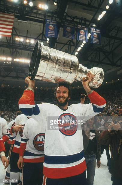 American professional ice hockey player Ken Morrow of the New York Islanders lifts the Stanley Cup over his head after his team won the NHL...