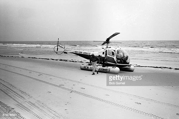 American public official and city planner Robert Moses disembarks from a helicopter on a Fire Island beach during a visit to a construction site...