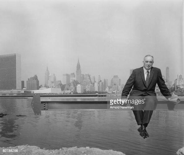 American public official and city planner Robert Moses poses for a portrait seated on a steel beam over the East River on Roosevelt Island New York...