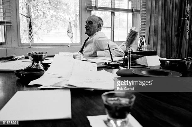 American public official and city planner Robert Moses sits at the end of a cluttered table in his office New York New York August 1962
