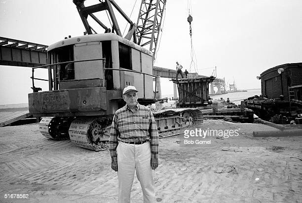 American public official and city planner Robert Moses stands in front of a crane at a construction site for a Long Island highway bridge probably...
