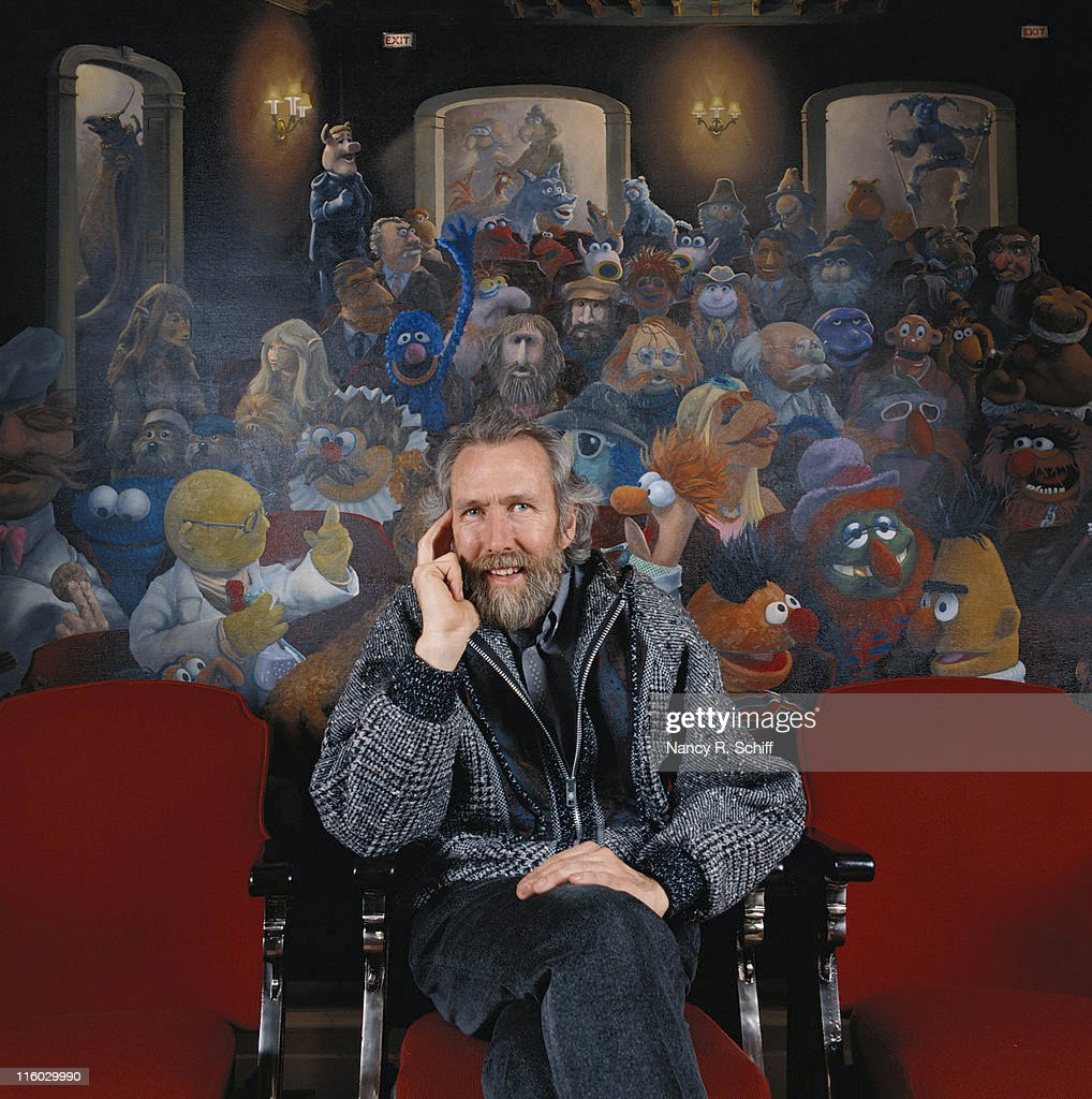 American puppeteer Jim Henson (1936 - 1990), creator of 'The Muppets' with a muppet mural behind him, 1986.