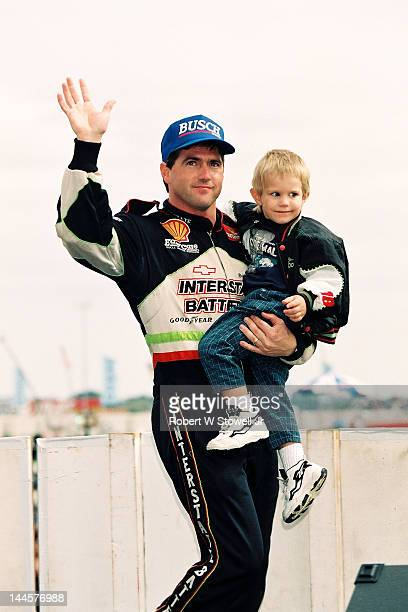 American race car driver Bobby LaBonte holds a child and waves at the Winston Cup Race at the Charlotte Motor Speedway Charlotte North Carolina 1997