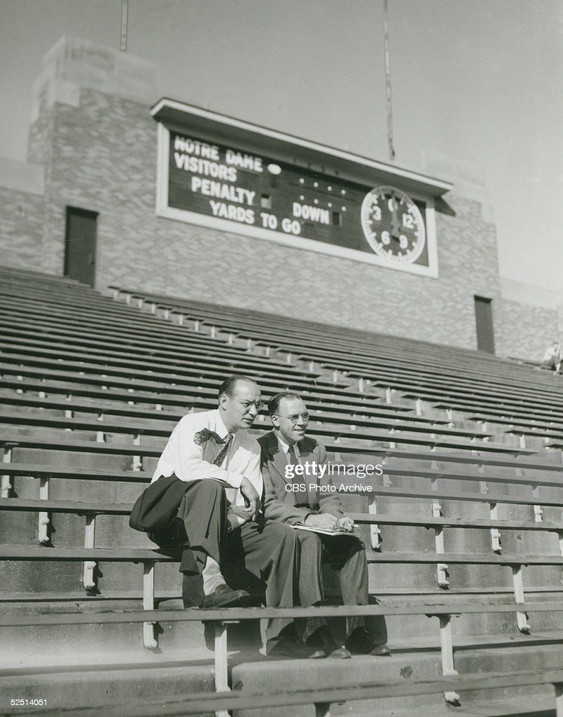 American radio sports announcers Ted Husing and Jimmy Dolan sit in the otherwise empty bleachers of Notre Dame Stadium in advance of a football game...