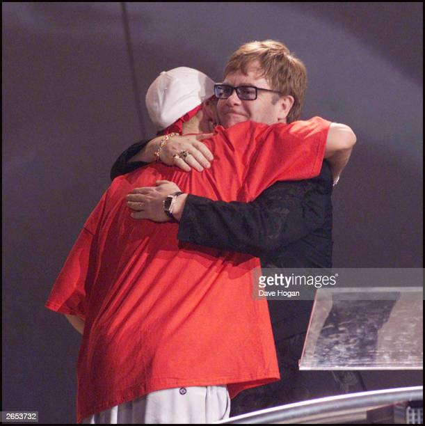 American rap star Eminem accepts an award from British musician Sir Elton John on stage at the 2001 Brit Awards held at Earls Court Exhibition Centre...