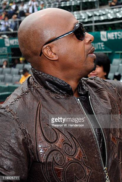 American rapper entertainer MC Hammer signs a replica bobblehead doll of himself for a fan before a MLB baseball game between the Los Angeles Angels...