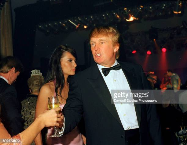 American real estate developer Donald Trump accepts a drink during a New Year's Eve party at the MaraLago estate Palm Beach Florida December 31 2002...