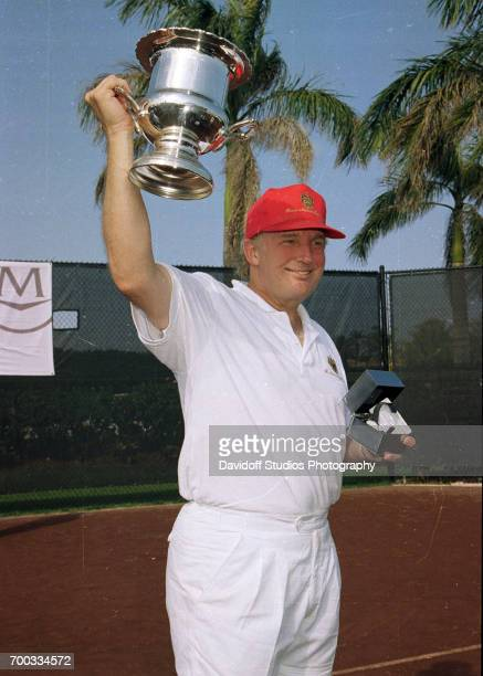 American real estate developer Donald Trump raises a trophy as he poses at the CapCure ProAm Invitational Tennis Tournament held on the MaraLago...
