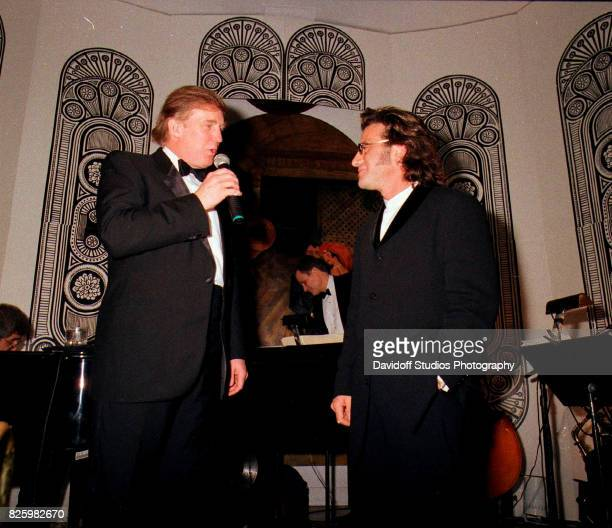 American real estate developer Donald Trump stands with musician Tico Torres on stage during a 'roaring 20's' party at the MaraLago estate Palm Beach...