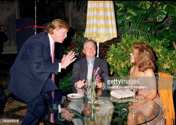 American real estate developer Donald Trump talks with television host Regis Philbin and his wife Joy at the MaraLago club Palm Beach Florida April...