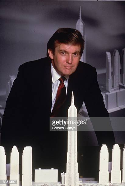 American real estate mogul Donald Trump posing with scale models of tall skyscrapers