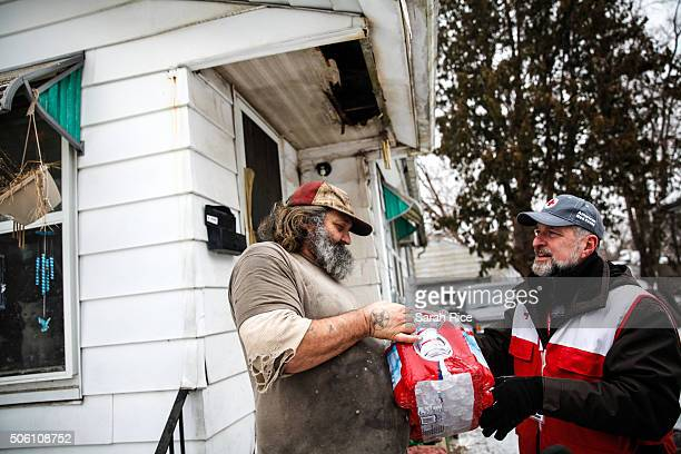 American Red Cross volunteer John Lohrstorfer right brings bottled water to Edward Yankee at his home on January 21 2016 in Flint Michigan The Red...