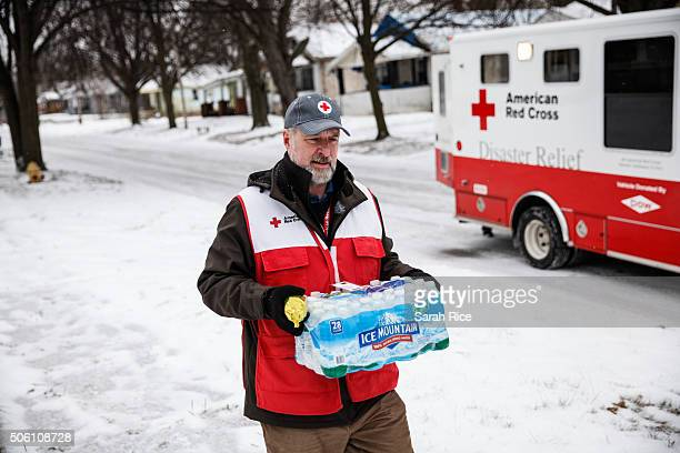 American Red Cross volunteer John Lohrstorfer walks down Maryland St on Flint's north side bringing bottled water and filters to homes on January 21...
