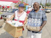 American Red Cross volunteer Mary Breslin of Michigan helps New Orleans resident Earl Davis carry food and cleaning supplies back to his car after he...