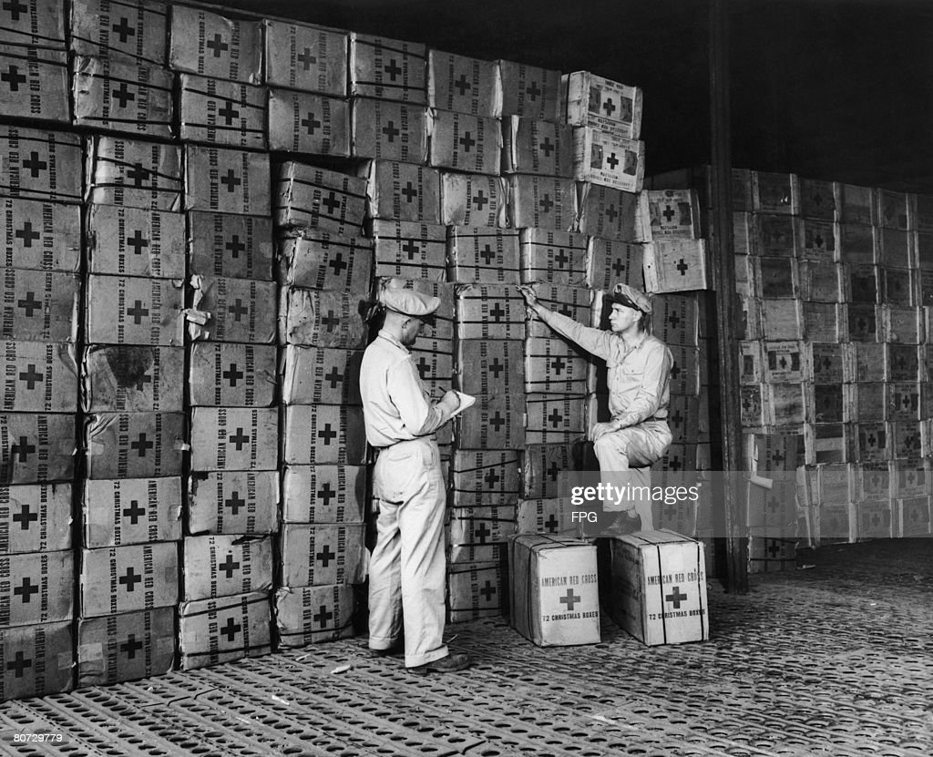 American Red Cross workers Ernest J. Perfins and Howard L. White at the organisations Dutch New Guinea base checking packages for troops fighting on Leyte and other islands in the Philippines, 20th November 1944. They hope to ensure that every soldier has a package for Christmas Day.