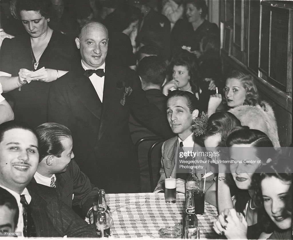 American restauranteur and social activist Sammy Fuchs (1904 - 1969) (standing, with bow tie) poses with patrons at his establishment, Sammy's on the Bowery, New York, New York, mid 1940s. (Photo by Weegee(Arthur Fellig)/International Center of Photography/Getty Images)