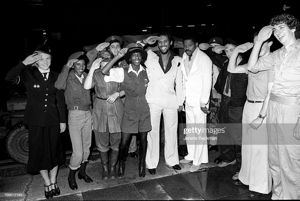 American rhythm and blues musicians John Whitehead (1949 - 2004) (in white suit of left) and Gene McFadden (1948 - 2006) (in white suit on right) pose for a portrait mid-salute with military personel and fans, England, mid 1979.