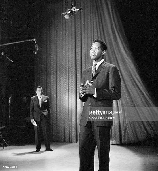 American rhythm and blues soul and pop singer Sam Cooke performs on the CBS variety show 'Toast of the Town' as series empresario Ed Sullivan looks...