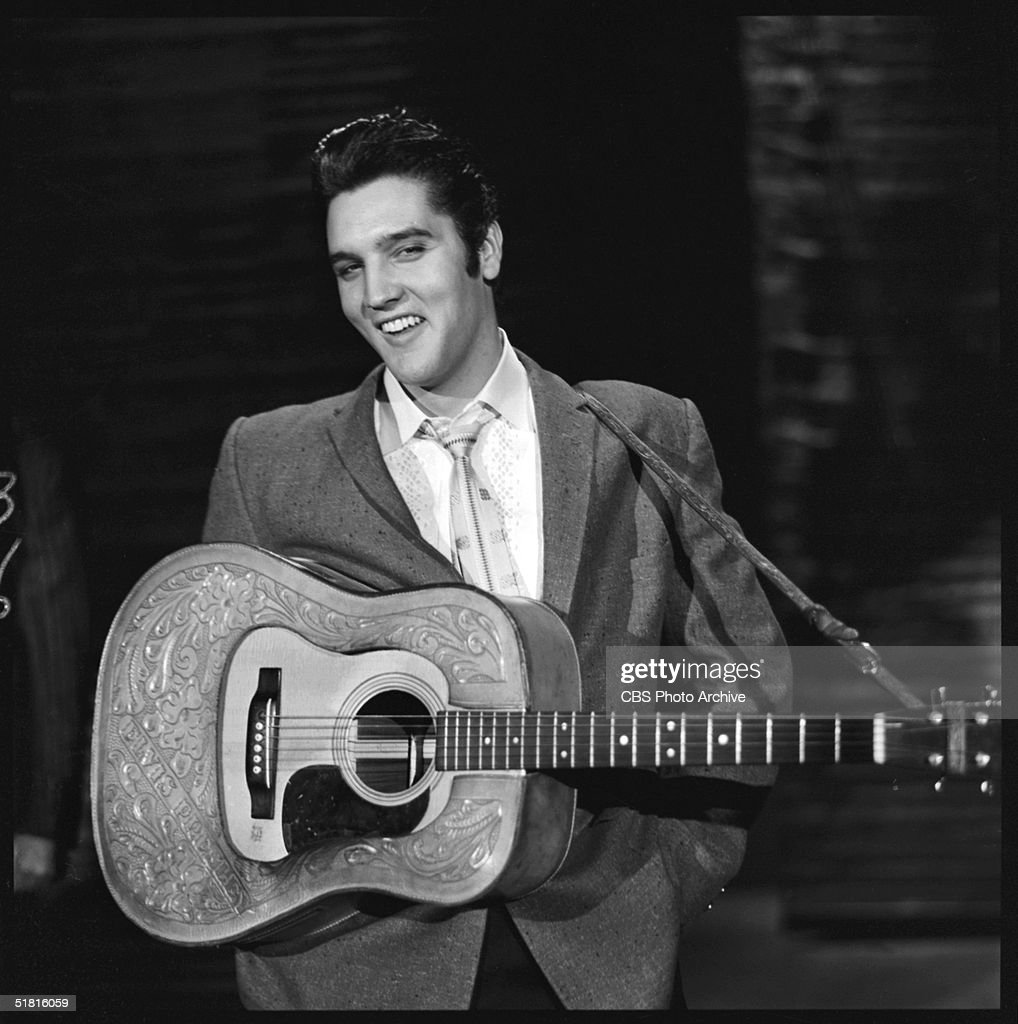 American rock and roll singer and actor <a gi-track='captionPersonalityLinkClicked' href=/galleries/search?phrase=Elvis+Presley&family=editorial&specificpeople=67209 ng-click='$event.stopPropagation()'>Elvis Presley</a> (1935 - 1977) smiles as he stands with his hands in his pockets and a guitar around his shoulders during his second appearance on the Ed Sullivan Show, New York, New York, October 28, 1956.