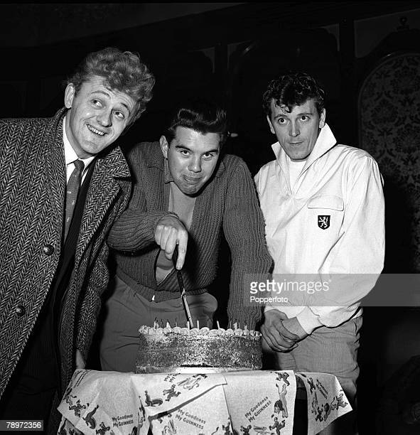 American rock and roll singer Gene Vincent cutting a cake as he stands with Lance Fortune and Willie Harris 1960