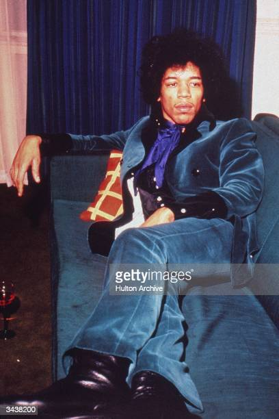 American rock musician Jimi Hendrix wears a teal velvet suit while reclining on a sofa