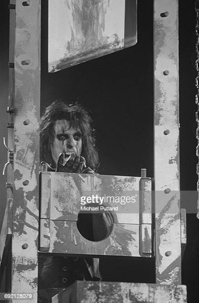 American rock singer Alice Cooper performing with a guillotine stage prop December 1986