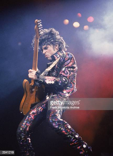American rock singer and songwriter Prince plays guitar on stage during a concert 1985