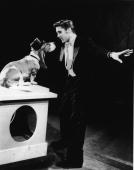 American rock singer Elvis Presley serenades a basset hound in a top hat with the song 'Hound Dog' on the set of 'The Steve Allen Show' July 1956