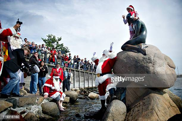 American Santa Claus'es take a foot bath at Hans Christian Andersen's fairy tale sculpture 'The Little Mermaid 'at Copenhagen Harbour on July 18 2011...