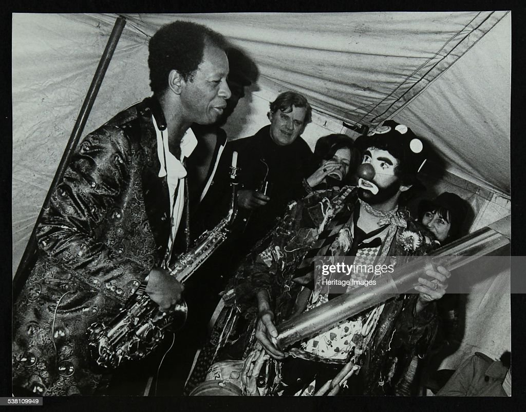 American saxophonist Ornette Coleman meets a clown, Bracknell Jazz Festival, Berkshire, 1978. Piano player and trombonist Eddie Harvey is in the background. Artist: Denis Williams.