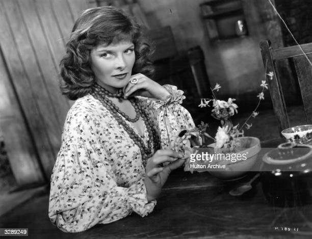 American screen actress Katharine Hepburn toys with a bowl of flowers in the film 'The Little Minister' directed by Richard Wallace for RKO Radio...