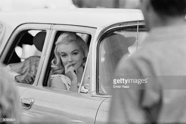American screen icon Marilyn Monroe in the front seat of a car during the filming of 'The Misfits' on location in the Nevada Desert