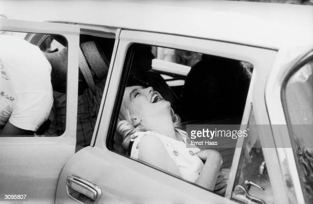 American screen icon Marilyn Monroe laughing in the front seat of a car during the filming of 'The Misfits' on location in the Nevada Desert