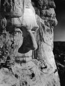 American sculptor Gutzon Borglum and several of his crew work on carving the head of American President Abraham Lincoln part of the Mount Rushmore...