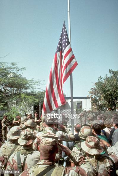 American servicemen salute as the national colors are raised again at the US Embassy following the retreat of Iraqi forces from Kuwait as a result of...