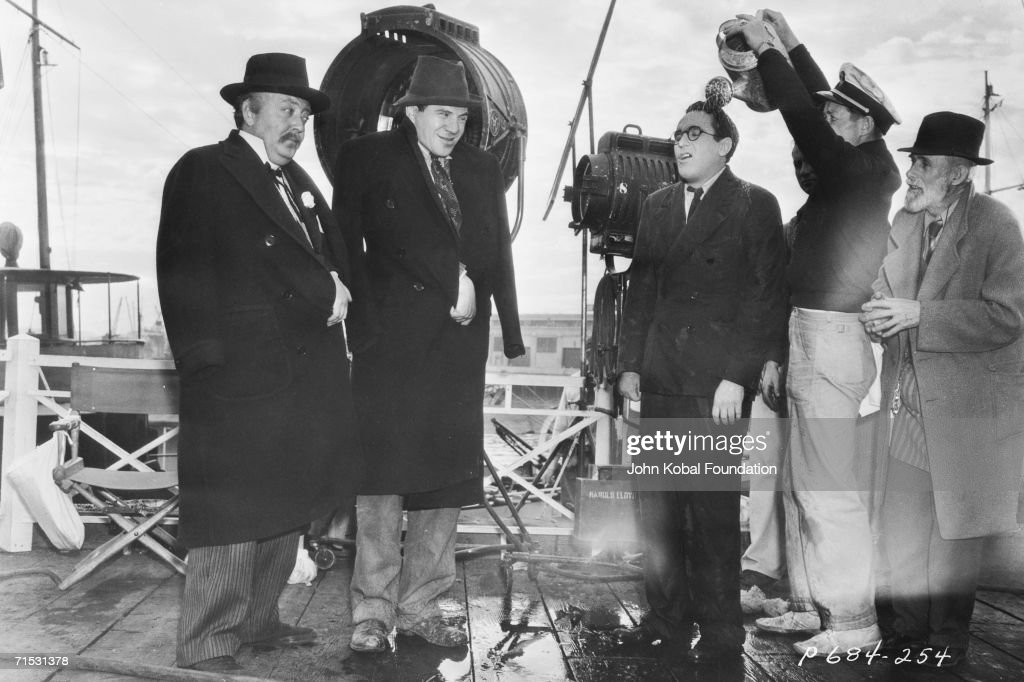 American silent era comedian Harold Lloyd gets a soaking from a watering can on the set of Paramount comedy 'The Milky Way' 1936 Watching are...