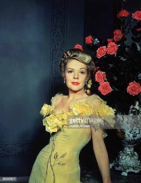 American singer and actor Alice Faye wears a yellow velvet saloon performer's dress with roses at the neckline while posing beside an arrangement of...