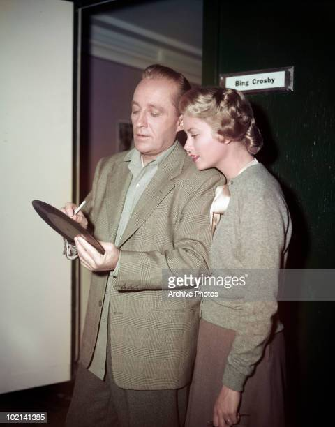 American singer and actor Bing Crosby signs one of his records for actress Grace Kelly during filming of 'The Country Girl' directed by George Seaton...