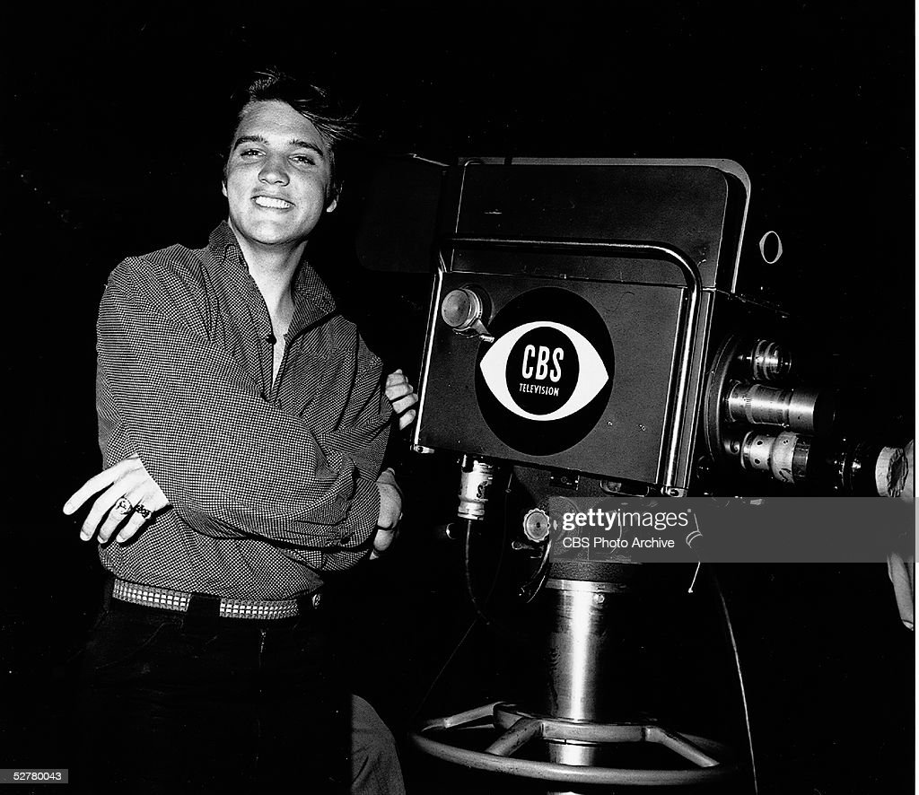 American singer and actor Elvis Aaron Presley (1935 - 1977) stands with his arms crossed by a television camera on the night of his first appearance on 'The Ed Sullivan Show,' CBS Television City studios, Los Angeles, California, September 9, 1956.