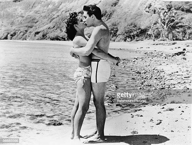 American singer and actor Elvis Aron Presley dressed in swimming trunks exchanges a passionate kiss with bikiniclad American actress Joan Blackman on...